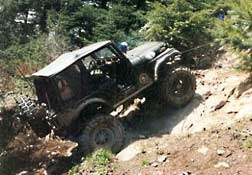 Black jeep being winched up hill